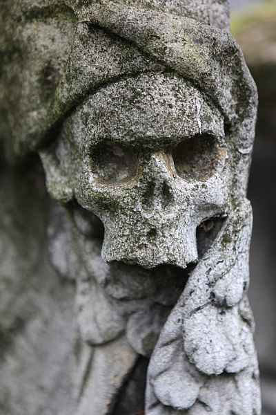 Worn cemetery sculpture at Bunhill Fields Burial Grounds in London, England.
