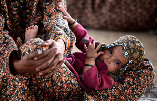 fotojournalismus:  An Indian nomadic Gujjar child and her mother, at a temporary settlement in Jammu, India, May 6, 2012. [Credit : Channi Anand/AP]