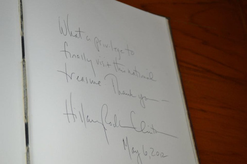 U.S. Secretary of State Hillary Rodham Clinton signs the guestbook at the Victoria Memorial Hall in Kolkata, India, on May 6, 2012. [State Department photo/ Public Domain]