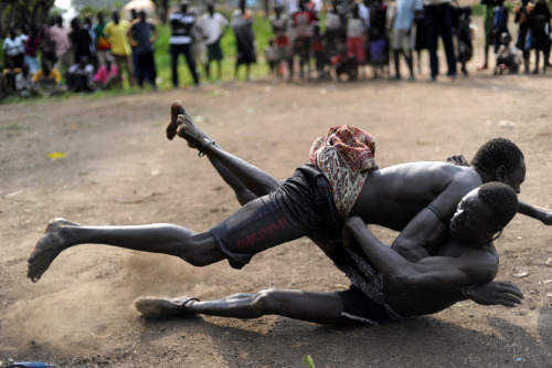 South Sudanese members of the Mundari ethnic group wrestle where the tribe brought cattle and sheep for sale in Juba on July 7, 2011, two days before South Sudan secedes. The Mundari are cattle keepers who live in the south and pride themselves in being good wrestlers. (Roberto Schmidt/AFP/Getty Images)