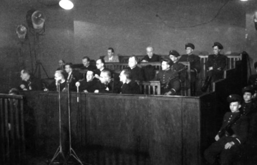 Photograph depicting accused Catholic priests during the Stalinist show-trial of the Kraków Curia, January 21-26, 1953The Stalinist show trial of the Kraków Curia was a public trial of four Roman Catholic priests – members of the Kraków diocesan Curia – including three lay persons, accused by the Communist authorities in the People's Republic of Poland of subversion and spying for the United States. The staged trial, based on the Soviet formula, was held before the Military District Court of Kraków from January 21 to 26, 1953 at a public-event-hall of the Szadkowski Plant.