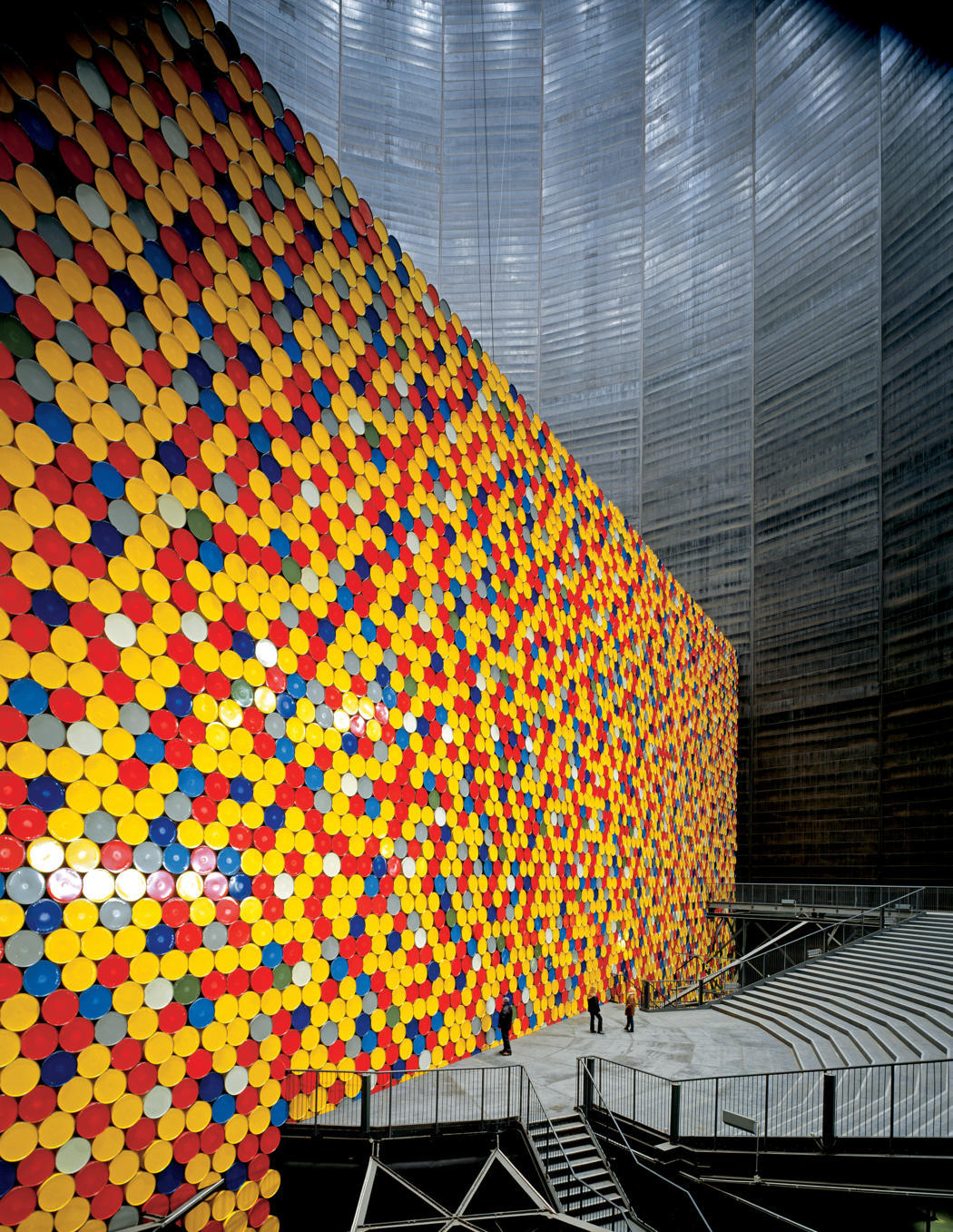 devidsketchbook:  Christo and Jeanne-Claude The Wall - 13,000 Oil Barrels, Gasometer, Oberhausen, Germany, 1998-99 Photo: Wolfgang Volz  The Gasometer, one of the largest gas tanks in the world, 360 feet (110 meters) high by 223 feet (68 meters) in diameter, was built in 1928 to store the gas (a by-product of the industrial production of iron ore). Christo and Jeanne-Claude were invited by IBA Emscher Park Organization (founded by the state of North Rhine-Westphalia in 1989 to improve the infrastructure of the Ruhrregion), to exhibit in the Gasometer in Oberhausen.