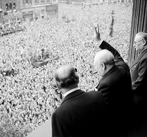 Winston Churchill giving a victory sign to a crowd assembled in Whitehall, London on VE Day, May 8, 1945.