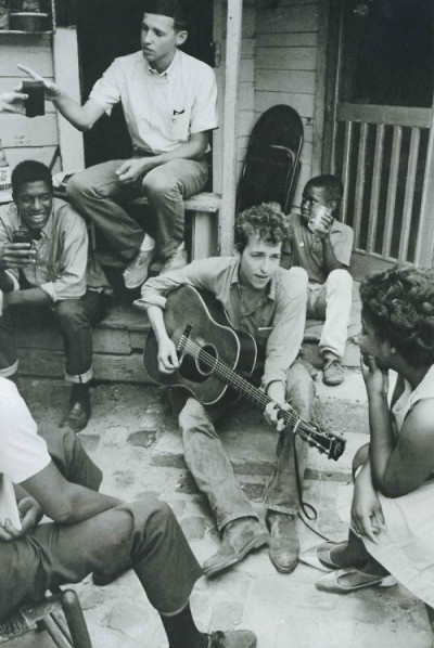 victimize:  Bob Dylan plays on the back of the SNCC office in Greenwood, Mississippi, 1963