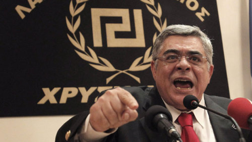 "Greek neo-Nazi orders removal of ""disrespectful"" journalists Journalists who refused to stand in respect for Golden Dawn party leader Nikolaos Michaloliako were forcibly removed from a recent press conference. Michaloliakos railed against the conservative Samaras party, illegal immigrants, and the mainstream press before heaping praise on the youth he believed responsible for Golden Dawn's election success. ""I want to dedicate this victory to all of our brave lads,"" he said, continuing, ""who wear the black t-shirts with the ancient letters reading 'Golden Dawn'.""(Photo via CBC News) source Follow ShortFormBlog: Tumblr, Twitter, Facebook"
