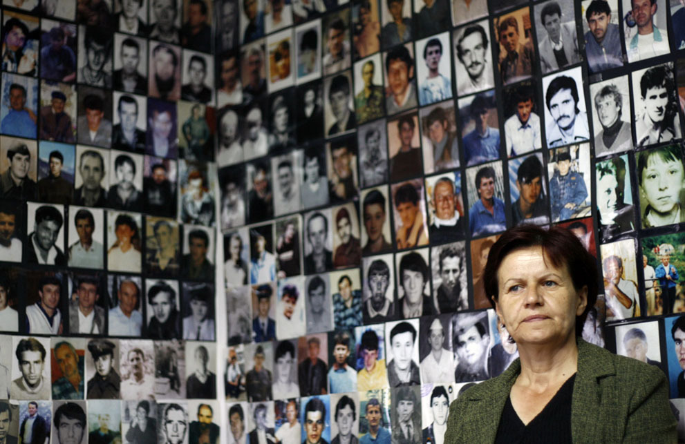 Dado Ruvic  A Bosnian Muslim woman from Srebrenica, sitting under pictures of victims of the genocide in the town during the 1992-1995 Bosnian war, watches the television broadcast of Ratko Mladic's court proceedings, in Tuzla, on June 3, 2011. Former Bosnian Serb military commander Mladic said he defended his people and his country in the Bosnia war and now intended to defend himself against war crimes charges at the U.N.'s Yugoslavia tribunal. Mladic was indicted over the 43-month siege of the Bosnian capital Sarajevo and the massacre of 8,000 Muslim men and boys in the town of Srebrenica, close to the border with Serbia, during the 1992-95 Bosnian war.