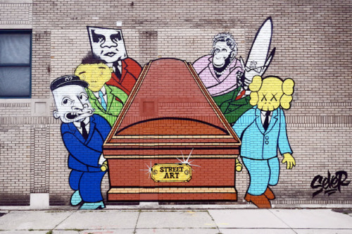 "Sever's Predicted Death of Street Art Mural in Detroit Originally shared via the Instagram feed of SABER, artist Sever looks to have been hard at work on a mural that pays a tongue-in-cheek tribute to other street art giants including Shepard Fairey, Futura, KAWS, Barry McGee and Os Gemeos. The mural shows the crew toting a casket branded with the insignia, ""STREET ART."" Each persona is seemingly dressed in business attire suits as they cart the oversized casket. Source: 12ozProphet.com"