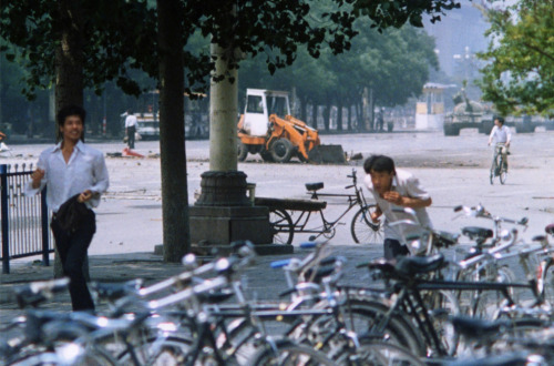 "so-a-la-ih: Terril Jones's view of Changan Avenue in Beijing on June 5, 1989, shows ""tank man,"" in the distance at left, framed by two tree trunks, on the verge of confrontation with the tanks in the distance at right. Mr. Jones's angle on the historic encounter is vastly different from four other versions shot that day, taken at eye level moments before the tanks stopped at the feet of the lone protester. Wildly chaotic, a man ducks in the foreground, reacting from gunfire coming from the tanks. Another flashes a near-smile. Another pedals his bike, seemingly passive as the tanks rumble towards confrontation."