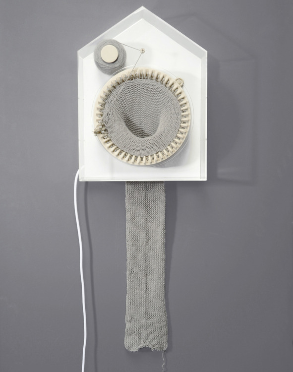 "365 Knitting Clock by Siren Elise Wilhemsen  ""365 is stitching the time as it passes by. It is knitting 24 hours a day and one year at the time, showing the physical representation of time as a creative and tangible force. After 365 days the clock has turned the passed year into a 2-m long scarf. Now the past can be carried out in the future and the upcoming year is hiding in a new spool of thread, still unknitted."""