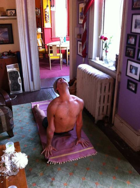 "Michael Joel Hall.  This is a shot of me in my home practice.    You can also find me at your office or agency doing Corporate Yoga Wellness with my company Mid City Yoga, at your gym (Balance!), or at your friendly yoga studio with a great non-profit mission (yoga district!).   I get to see some really different aspects of DC Denizentry— from the Black Cat's Red Room to the World Bank's four walls.  I reckon it comes as no great surprise that there is a need for mindfulness practice in a town like DC.  Washington, DC is a notoriously goal-oriented town (dare I say ""type-a"") town. What continues to inspire me, is how much levity and good humor these driven practitioners bring to their mat.  Able to put away hard-instilled ""Type-A""ness behavior  and bust out some non-Brooks Brother equanimity and togetherness for a few breaths and postures, DC Yoga gives hope. Please forgive the platitude, but we know that paths are many. And, duh, truth is one. Different points of view and passions coming together to revel in a common path towards peace? Insert your own Congress joke here.   Oh, DC yoga, I love you."