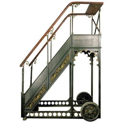 c. 1890.  Bernard Rolling Library Ladder. Iron and wrought iron. France. Cast Iron in forest green with perforated metal sides, decorative cuts and wrought iron balustrades with brass embellishments. Stained oak steps and rails with a top shelf. Hand-painted details in gold and black.