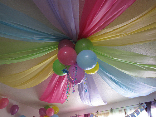 DIY Rainbow Birthday Party Ceiling. I had to post this because it is from a Rainbow Unicorn Party. How perfect! Anyway, cheap plastic table cloths were used instead of streamers, then gathered in the middle with balloons. For tons more photos of this rainbow unicorn themed party go to Cafe Mom here.