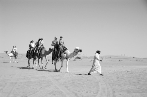 The man leading the camel ride.