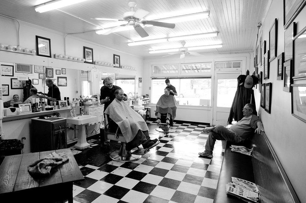 Photo of the Day: Two barbers at South End Barber Shop cut hair. Everyone talks about high school football and local hunting spots. Photograph by Aaron Cress (Salisbury, North Carolina), January 2011, China Grove, North Carolina