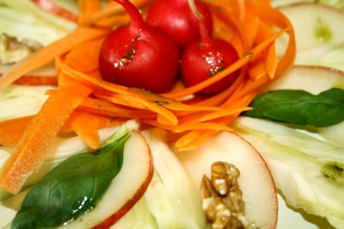 Fennels, red pears, carrots and radishes salad with basil and walnuts
