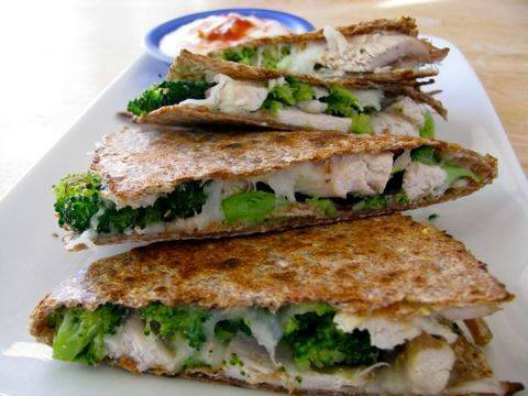 cleaneatz:  Broccoli and Chicken Quesadillas Ingredients 2 ounces of pre-cooked shredded chicken ½ cup of steamed broccoli, chopped up 1/3 cup of part skim shredded mozzarella cheese 1 whole grain tortilla 2 tbsp plain, no fat Greek yogurt 1 tsp red pepper sauce Directions Combine Greek yogurt with hot sauce and set aside. Heat chicken and broccoli in a large non-stick pan over medium heat. Once heated through remove from the pan and place in a medium bowl. Toss chicken and broccoli with salt, pepper and garlic powder and then set aside. Place tortilla in the hot pan and allow to heat through on one side. Flip the tortilla and sprinkle half of the cheese over one half of the tortilla. Top cheese with broccoli and chicken and then sprinkle the rest of the cheese over the top. Using a spatula fold the tortilla over on to itself (into a half moon) and top with something heavy (ie. A weighted pan or my personal favorite, a teakettle). Allow to cook for a minute or two OR until the bottom lightly browed. Flip the tortilla and cook for another minute or two on the opposite side. Remove Quesadilla from the pan and allow to cool for a minute or so before cutting into wedges. Top with spicy yogurt and Enjoy!! Nutritional Analysis Calories: 390; Total Fat: 13.6g; Saturated Fat: 6.2; Cholesterol: 74mg; Sodium: 451mg; Carbohydrate: 29.1; Dietary Fiber: 6.1; Sugars: 1.7; Protein: 36
