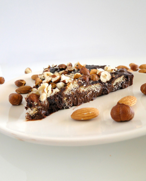 Chocolate Biscuit Cake Topped With Nuts Source - http://www.chichoskitchen.blogspot.com/2012/05/chocolate-biscuit-cake-topped-with-nuts.html  Ingredients: 200 g (7 oz) tea biscuits (I used McVitie's brand) 85 g (6 tbsp) unsalted butter 400 g (14 oz) bittersweet chocolate 23 cl (1 cup) heavy cream 1/2 cup hazelnuts and almonds, chopped  Grease 8-inch round springform pan with melted butter then line it with parchment paper.  Break the biscuits so they become crumbs but not powder.  In a small saucepan, melt the butter and the cream on low heat. When the butter is melted, add the chocolate pieces and let it melt on low heat.  Add the crumbled biscuits and stir until coated then pour the preparation into the prepared pan.  Top with the chopped nuts and place in the fridge for at least 3 hours. Cut into slices and serve.