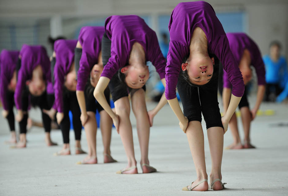 We can't do this. Can you? Students stretch during a training session at a gymnastic course at Shenyang Sports School in Shenyang, Liaoning province, China. Some 60 students, between the ages of 6 to 15, undergo a nine-year gymnastics program which includes foundation courses and gymnastic training courses at Shenyang Sports School, and those who are outstanding may be selected to join the national team.