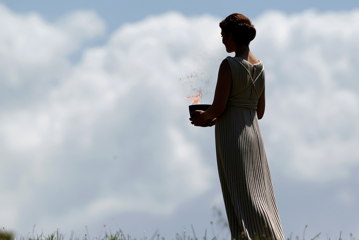 From Lighting the 2012 Olympic Flame, one of 19 photos. A priestess holding a lit cauldron performs in the final dress rehearsal for the lighting of the flame held on May 9, 2012, in ancient Olympia, Greece. (AP Photo/Petros Giannakouris)
