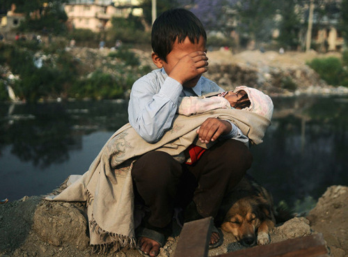 politics-war:  A boy cries as he holds his sister in his lap after a confrontation between squatters and police.