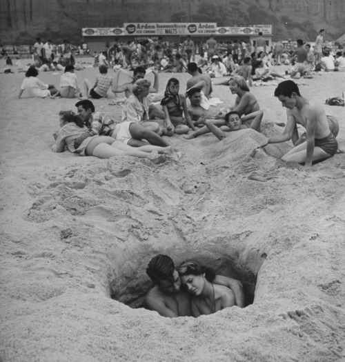 commovente:  Young couple cuddling as they sit down in a hole in the sand while others lie around behind them on a hot Independence Day at the beach. Photo by Ralph Crane, 1949.