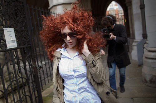 A woman wearing a large red wig performs a stunt in front of the media outside the high court where Rebekah Brooks is giving evidence to the Leveson inquiry. Brooks was also greeted by a pantomime horse, a reference to the news earlier this year that David Cameron rode a retired police horse that had been loaned to Brooks Photograph: Dan Kitwood/Getty Images
