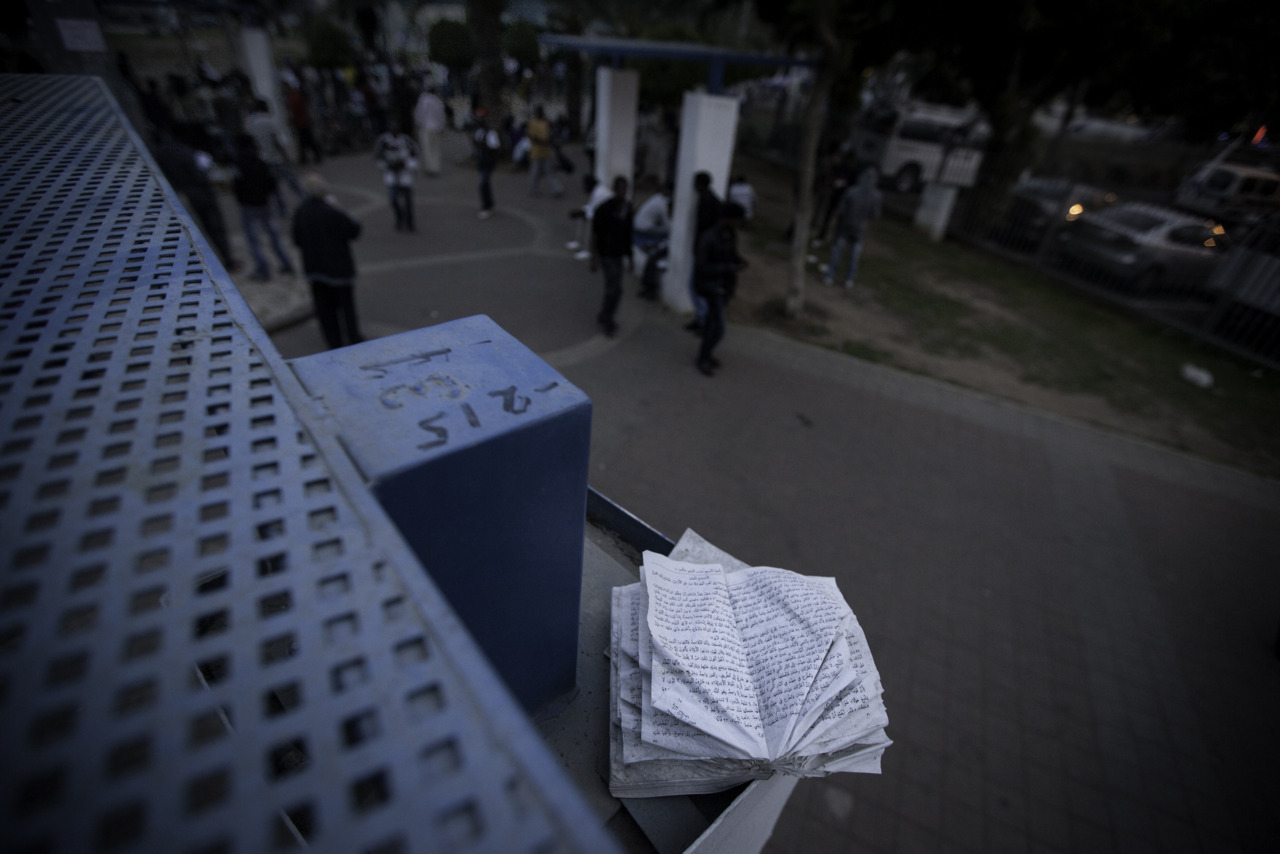 A man's hidden Koran sits perched on top of a bench shelter overlooking a park in Shapira where refugees wait in line for food provided by the community.