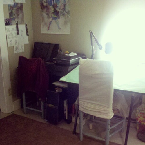 "Brand new #studio set up. Loving all the room. #illustration #drawing (Taken with instagram) Little explanation: I have an Asus hooked up to an amazing flatbed scanner (new this year) that I use for importing all the work I make traditionally.The drafting table was an awesome find, a heavy duty fold-up style for $3 at a yard sale. Those are the most uncomfortable wicker-seat chairs I sit on. They were hand-painted in Mexico, and I appreciate the craftsmanship. But, I hate them. What you don't see to the left is a 5'5 ferret cage. To the right will go a table with a 32"" screen. Plus, eventually my HP printer. The great thing about drafting tables is that they can easily be converted into a flat surface, so I could package prints and merch or work on other crafts. It'll be very handy when I need to cut paper and assemble comic books! Hoorah."