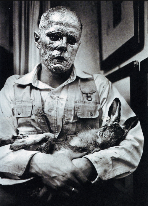 cavetocanvas:  Joseph Beuys, How to Explain Pictures to a Dead Hare, 1965 One of the artist's most famous performances, Beuys covered his head first with honey, and then with fifty dollars worth of gold leaf. He cradles a dead hare in his arms, and strapped an iron plate to the bottom of his right shoe. Viewed from behind glass in the gallery, the audience could see Beuys walking from drawing to drawing, quietly whispering in the dead rabbit's ear. As he walked around the room, the silence was pierced by intermittent sound of his footsteps; the loud crack of the iron on the floor, and the soundless whisper of the sole of shoe. (via)  forever my favorite