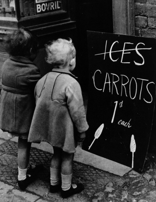 Two little girls read a board advertising carrots instead of ice lollies due to wartime shortages of chocolate and ice cream, 1941. Getty