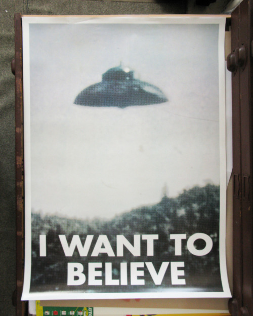 Terrible Poster Week Concludes: I WANT TO BELIEVE This is an authentic reproduction of Fox Mulder's office poster from the TV series the X-Files. Or so I thought. I bought this online awhile back, but it is only now (because of this post) that I did any digging. A cursory google search suggests that this poster is not original and never appeared in an X-Files episode. So this poster is bogus! Wait, no. This poster is a HOAX! Man, do I feel silly. This is what the REAL one looked like; well to be more accurate, there were 2 versions of the poster that appeared in the series. Designer…UNKNOWN.