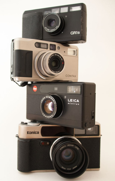 Titanium-black-titanium-black stack of: Konica Hexar AF Titantium, Leica Minilux, Contax TVS, Ricoh GR1s. Don't try this at home, kids! Seventeen cameras were destroyed in the making of this photograph. These are all great street shooters, but with the amount of 35mm film I'm shooting dropping into the single digits per month, I feel these will all soon be looking for a new owner.
