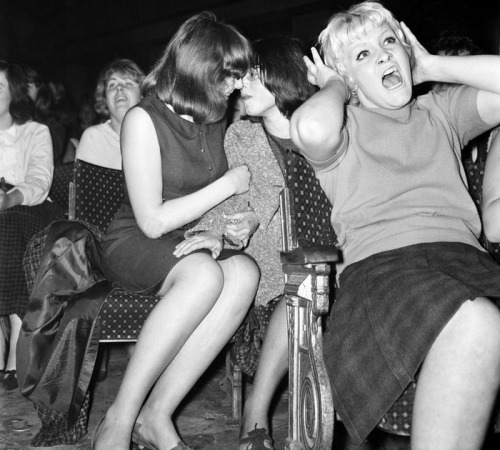 itsraininbritishmen:    A couple only have eyes for each other at a Beatles concert in Wigan, 13 October 1964.  #i don't know what i like more; vintage lesbians or the lady in front going fucking apeshit  both. both is good.