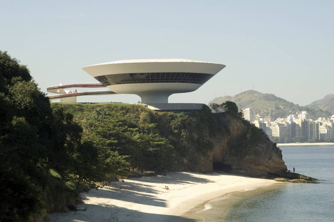 "Niterói Contemporary Art Museum Also Known As: Museu de Arte Contemporânea de Niterói (""MAC"")Location: Niterói, Rio de Janeiro, BrazilCompleted: 1996Architect: Oscar NiemeyerStructural Engineer: Bruno Contarini About the Niterói Contemporary Art MuseumSuggesting a sci-fi space ship, the Contemporary Art Museum in Niterói seems to hover on top of a cliff. Winding ramps lead down to a plaza."