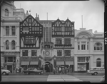 London Court, St Georges Terrace, Perth ca.1955 Street scene showing pedestrians waiting at zebra crossing, shoppers, motor vehicles, City Mutual Life Assurance Society, Wattle Restaurant, (no. 62); faux-Tudor façade of London Court; National Bank, (no. 48)