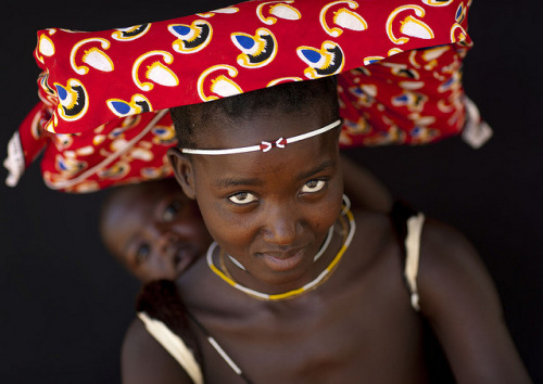 dynamicafrica:  A Mucubal woman from Angola carrying her baby on her back.