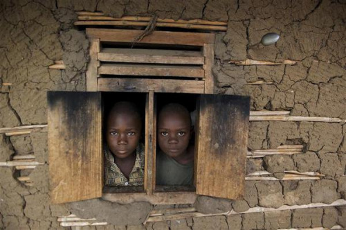 unicef:  Boys peer through a window in their home in Busoru III Village, a former displacement camp. Children in Uganda continue to face persistent poverty and high rates of infant and child mortality. Despite reducing child mortality rates by 27 per cent since 1990, Uganda will not achieve Millennium Development Goal 4 – the goal to reduce by two-thirds the deaths of children under age five.2919 © UNICEF/Shehzad Noorani http://www.unicef.org