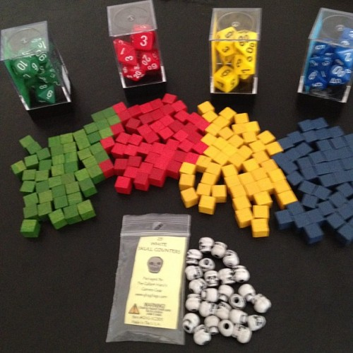"Watch Your Six components: wooden cubes, polyhedral 7-die set for each player, and skull counters—a ridiculous bargain at 25 for $1.99. (Taken with instagram) The cubes were borrowed from Carolus Magnus, a terrific Euro abstract strategy game that Deke has absolutely no interest in ever playing, so they won't be missed. The skulls will lend a bit of a sinister edge that will be sorely needed to counter the cuteness of the Lego minifigs we'll be using for character pieces. And the dice? Well, they'll be needed for darn near everything, so rather than putting a random collection of stuff cobbled from other games, I thought I'd spend a few bucks so something in the game (beside the board) would feel distinctly new. Still, we're at about $19 in production costs for what would probably cost $50-$60 in the store. The real problem now is that the rules—though chock-full of things he likes to do—are having the aggregate effect of feeling like a game of Calvinball. (Or, as Kim astutely put it, ""you've invented True American the Board Game."")"