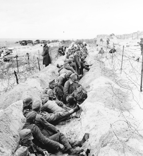 opacasilentianoctis:  German prisoners in a shallow sand pit on the coast of France.