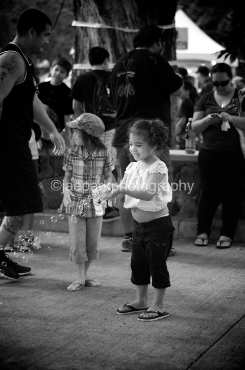 "Bubbles Make Me Happy.  I noticed this girl at the last Punahou Carnival who was having such a grand time blowing bubbles.  It made me think about how much we lose as we grow older and taken on the burdens of ""living"" life.  Its always the simple things that bring us the most joy, but as we grow older, we surround ourselves with this complexity and more physical goods on the road to trying to make ourselves happy again.  Maybe we need to go back to the simple things.  Taken with my Nikon D7000."