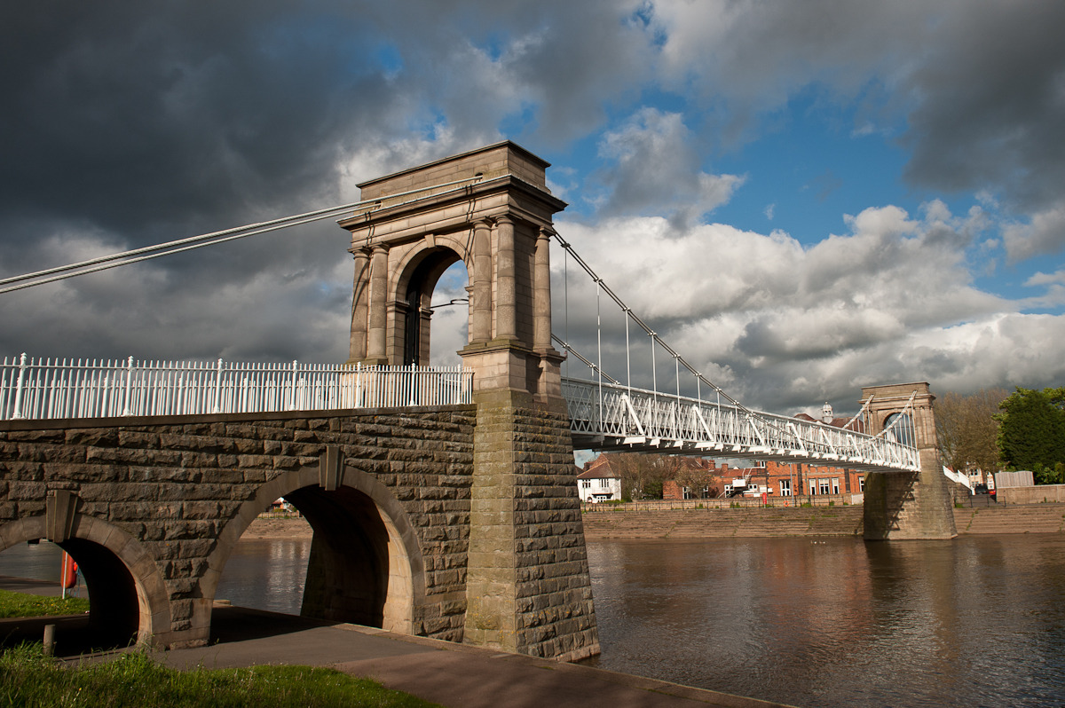 WILFORD SUSPENSION BRIDGE, NOTTINGHAM: personal shot from May 2012 Just a photo I took on the way into town last week. Wilford Suspension Bridge is near my flat. I love days when the sun creeps through gloomy clouds and you get this slightly surreal light. I now have 'Sunshine On A Rainy Day' in my head. Damn.