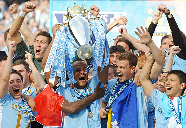 Manchester City captain Vincent Kompany lifts the Premier league trophy and celebrates with Edin Dzeko (2nd R), Sergio Aguero (R) and Samir Nasri (L) after their 3-2 victory over Queens Park on Sunday. Manchester City won the game 3-2 to secure their first title since 1968. This is the first time that the Premier League title has been decided on goal-difference, Manchester City and Manchester United both finishing on 89 points. (Paul Ellis/AFP/Getty Images) BERLIN: Manchester City breaks 44-year title drought