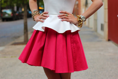 White peplum top and bright pink circle skirt. Heavy on the jewellery.