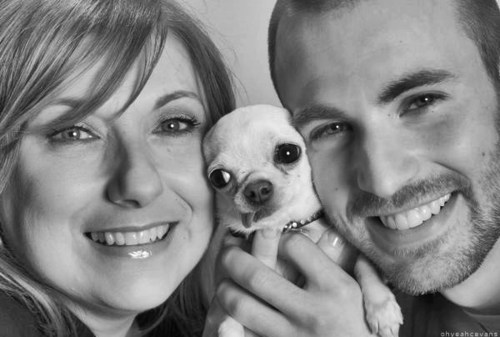 "Chris Evans and his mom (with bonus Puppy in the middle!) Now we all know where he gets his good genes and manners from :P ======= Chris Evans' Mom Talks About Her Son ""The Avengers"" is the latest in a series of blockbusters that have turned Sudbury native Chris Evans from superstar into superhero.In fact, millions now know Evans as Captain America, protector of the nation. Butoff-screen, his mother, Lisa, said he still cares most about small-town Sudbury and the people in it.""This is true for all four of my children,"" she said. ""They love this town. They love their childhood experience. It's pretty hard not to be happy in a house where there's always music, there's always performance.""Puppet shows and plays in the basement as children inspired big sister Carly to take the stage. Their mom remembered, Chris was starstruck.""He saw Carly performing when she was a little girl,"" she said. ""And he said, this great! She's getting all kinds of attention. She's getting candy and flowers. I want to do this.""Carly supported her younger brother's interest, but on her terms.""Honestly, I was in charge,"" she said, smiling. ""I was the director and he was my actor.""Carly is an actress herself as well as a drama teacher at Lincoln-Sudbury Regional High School. As kids, she brought Chris to his first audition. They even shared the stage in his first production at Concord Youth Theater.""Chris' talent —- I mean, that's a lot of raw talent,"" she recalled. ""And he had it from the time he was young.""Through high school, he and his three siblings performed. At age 17, Chris told his mom he was graduating early to move to New York City as an actor.""Got to do what you got to do,"" Lisa said. ""It was hard. It was hard to be supportive but I just made sure seven days a week, his days were filled.""Connections in New York led to roles in Los Angeles. Today, Chris is the star of a blockbuster franchise that could last another decade.""It's surreal,"" Lisa said. ""It's strange. It's exciting. It's all of those things.""And to cope with the chaos of his celebrity life, Chris always returns home —- to either his condo in Boston or his mom's.""This is what he does,"" Lisa explained about her son's routine in Sudbury. ""He sits in front of the TV. He watches the Celtics. He watches the Patriots. He walks his dog and he does nothing.""He even pays for the home's maintenance so his mom won't be tempted to sell it and downsize.""All of his friends are local,"" Lisa said. ""Chris' closest friends are his oldest friends. And so once again, I have a house full of them.""She then added, whispering, ""He still has his bedroom, which he wouldn't let me change."" Source Video"