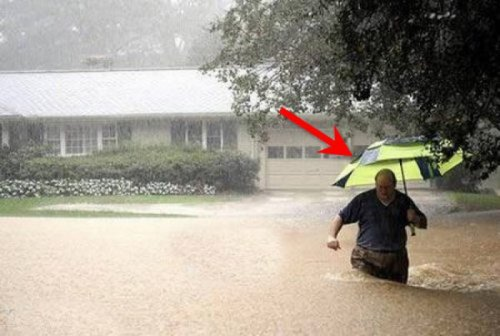 Guy Walking through Flood with Umbrella Gotta stay dry.