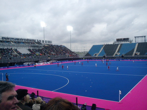 "England vs. India - Hockey at the Olympic Park Last week I went to visit my friend @BlueSkyBlues in London, because he had tickets for the final day of the London Prepares: Visa International Invitational Hockey Tournament at the Olympic Park, which was part of a series of warm up tournaments to test out how things would work before theactual Olympics start. The Olympic park is a strange place - it feels like a mixture of the swish bits of Birmingham, Milton Keynes, and a festival of some kind. It's hard to pin down because obviously it wasn't the full event, and the park isn't quite finished yet, and I imagine it will feel completely different when the Games are underway, but right now it feels very artificial. And it doesn't really feel anything like London either… Either way though, I had great fun! We arrived a bit late, but still saw most of  England vs. India in the Bronze medal match (which England won 2-1), and all of Germany against Australia in the final (which Germany won 5-2). The atmosphere was remarkably good (even though only three of the four the grandstands were full) with a small brass band playing Indiana Jones, The Great Escape, the Wallace and Gromit theme tune, and host of other crowd pleasers, with people clapping and cheering along. And the rain held off, thankfully, even if it wasn't particularly warm! And yes, the pitch really is neon pink and blue astroturf. Apparently though, the official name for that particular pink is ""London Pink""…"