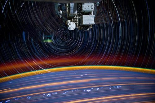 "Psychedelic space station stars and cities Astronaut Don Petit took the pictures to make this composite. Basically, it's a series of eighteen 30-second exposures added together so the motion of the ISS around the Earth makes the stars trail, the cities blur, and your mind expand, dude. The brown and green glow over the horizon is the atmospheric aerosol layer; molecules that absorb sunlight during the day and release that energy at night. The red glow above that puzzles me; I've written about it before. It might be a reflection of lights from inside the space station, but I suspect it's actually the aurora; it follows the curve of the Earth, and as you can see from the star trails the camera was pointed toward the poles — the direction you're likely to see an aurora. You can see faint star trails above the bright ones too, with a different center of curvature — those probably are from an internal reflection. Either that or the camera got moved, but that seems unlikely! This picture is one of several posted to Flickr, including this one which looks like it's from the last scene of ""2001: A Space Odyssey"". But they're all worth looking at, if only for their alien beauty. After all, the photographer was literally high when he took them! Image credit: NASA"