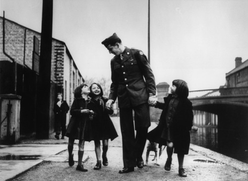 An American soldier with war orphans 'adopted' by his unit, London, 1943. Robert Capa