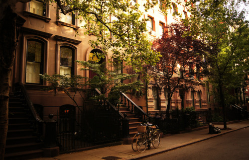 "Summer on Perry Street. Greenwich Village, New York City  On summer days like this, the bright summer sun barely cuts through the branches of trees canopies that line the street while brownstones and bicycles revel in the cool shade.   Some people flee the city in the summer, preferring cooler climates free of hot cement. For me, there is nothing that comes close to summer in the city.  It's true that often the air is held captive by the high heat and the sun scorches the pavement but when a breeze is allowed free rein to fly through the trees, something magical happens.   Streets breathe a sigh of relief and warm tones of muted sunlight cast upon buildings languishing in the shade inspire smiles of contentment.    —-  View this photo larger and on black on my Google Plus page   —-  Buy ""Summer in the City - Perry Street - Greenwich Village - New York City"" Prints here, email me, or ask for help."