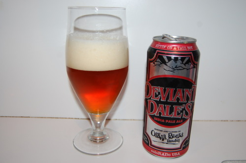 #336: Deviant Dale's – Oskar Blues Brewery, Longmont, Colorado I need to get a few more Oskar Blues brews on the resume. To date, I've had Dale's Pale Ale, Old Chub and the pilsner. All very nice, but there's quite a few heralded beers missing, and I'd like to change that. So Deviant Dale's, an 8% ABV double IPA, caught my eye on account of the fact that it's in a bigger can. Yep, call me a sucker. I'm that guy this beer was marketed to. Regardless, I have it now, so let's take a look. This one poured out with a slowly-building, off-white head, which built up a greater deal of foam than I was anticipating by the time it was over. Seemed a bit shy at first, but perked right up in the end. And a nice color we've got here, too. Ambery/orange appearance, a little coppery with just a bit of haze noticeable. You will be greeted by familiar notes once you start nosing about; grapefruit, orange and such, but there's a hint of something a little more. Perhaps a bit of caramel tucked underneath that, but there's a hint of something a little more herbal in a green, almost thyme-like way. That peculiar herbal note fade once beer meets palate, but it's for a good cause, because we've got a very, very well-balanced beer on our hands. As I've said before, my favorite double IPAs are usually doubled up on both hops and malt, not just hops. This one fits the bill. And it wastes absolutely no time. Up front, you get a nice whack of toffee and caramel, joined by all of those familiar American hop flavors; mostly pine and grapefruity citrus here, prickling the tongue through mid palate in a generous manner, but it's all held in check for all of its bigness. It never quite crosses the sticky, resiny threshold. Instead each force is wrapped up in one another, leveling out the other. Big, yet balanced. The finish, while certainly bitter, leaves a lot more sweetness and hop-derived flavors sticking around. The Verdict: Well worth trying, and if you're into double IPAs, well worth making a part of your rotation. Would I choose it over Double Trouble? Probably not, but then again I wouldn't choose any double IPA over Double Trouble. Still, this is quite good. Big and balanced.